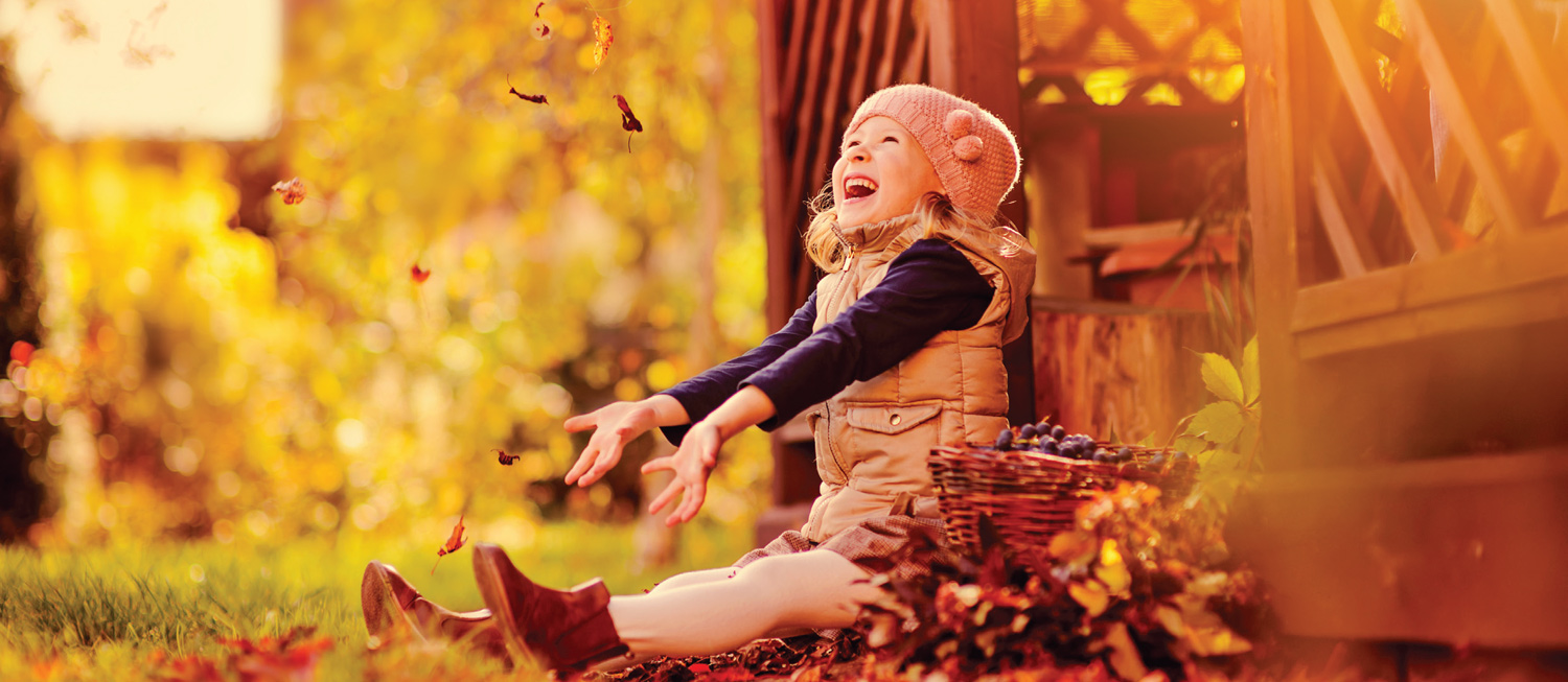 Child throwing leaves and smiling, enjoying the fall season